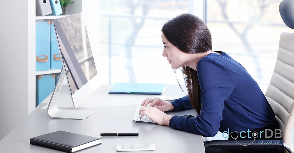 woman leaning forward and working on computer