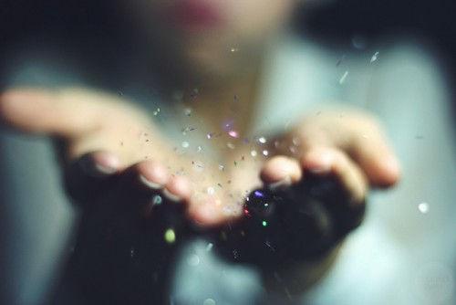 woman-hands-blowing-glitter-e14248173285