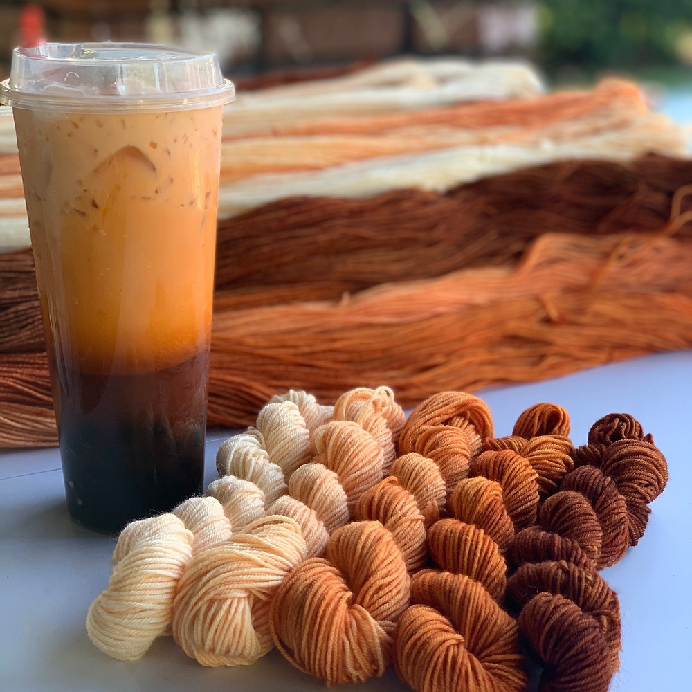 A cup of Thai iced tea and five small skeins of yarn, in a gradient of colors matching the tea.
