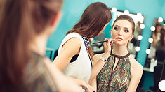 makeup artist putting on makeup on bride