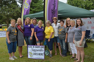 Alice in Dairyland poses with supporters outside at a fair booth