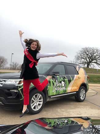 Julia Nunes, Alice in Dairyland, poses infront of the Alice in Dairyland Corn Promotion Board Car