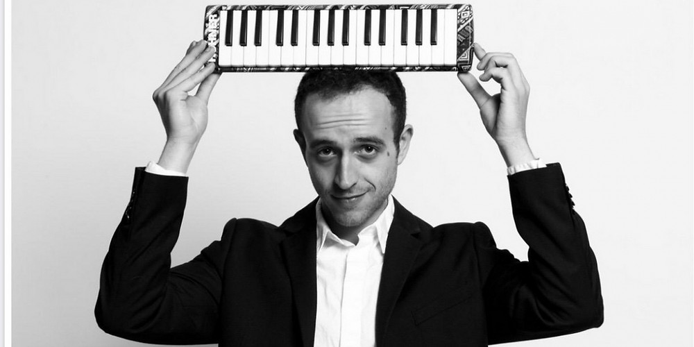 A man in a suit holding a small piano keyboard over his head