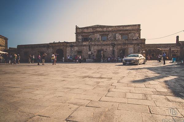 la piazza di Marzamemi in Sicilia, sicily, la sposa sta arrivando davanti alla chiesa per il suo matrimonio