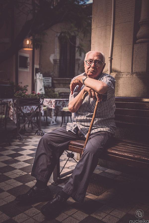 un signore anziano attende in piazza a castelmola taormina sicilia sorretto dal suo vecchio bastone