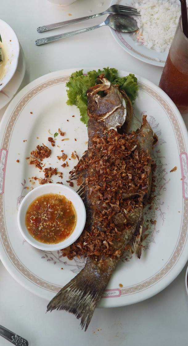 Deep fried whole fish topped with pepper and garlic