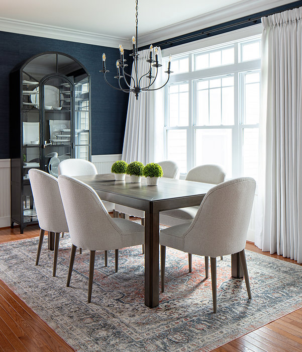 navy dining room, white upholstered dining chairs, dining table, metal chandelier, modern china cabinet, black metal cabinet, paned cabinet, white pinch pleat drapes, white curtains, area rug, seating for 6, grasscloth wallpaper, crown molding