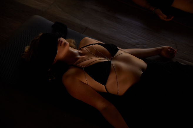 Women with black bra in Shavasana with blindfold