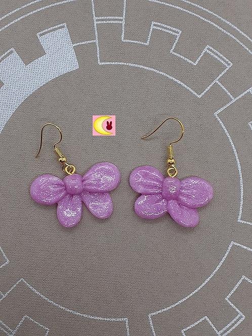 paire de boucles d'oreilles violet à paillettes en forme de noeud