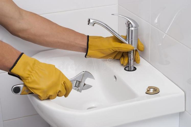 plumber-installs-new-faucet-sink-installation-faucet-sink-103738239.jpg