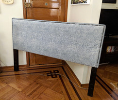 Reupholstered headboard with nail head trim.