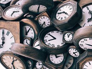 Relógios antigos de madeira amontoados.