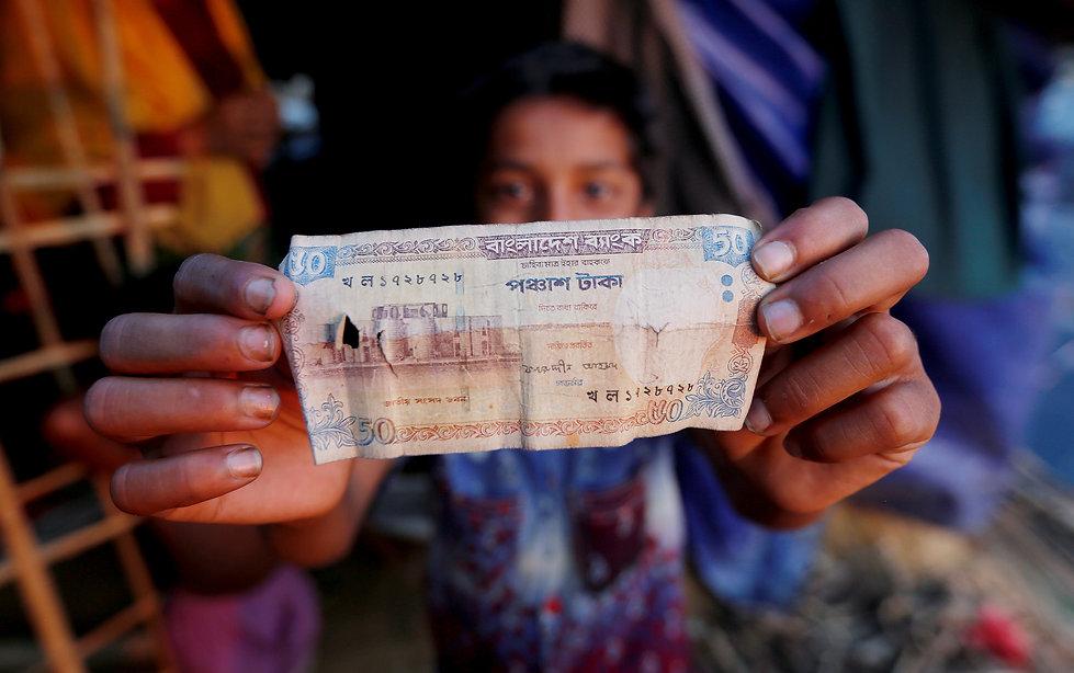 A Rohingya refugee displays a 50 Banglad