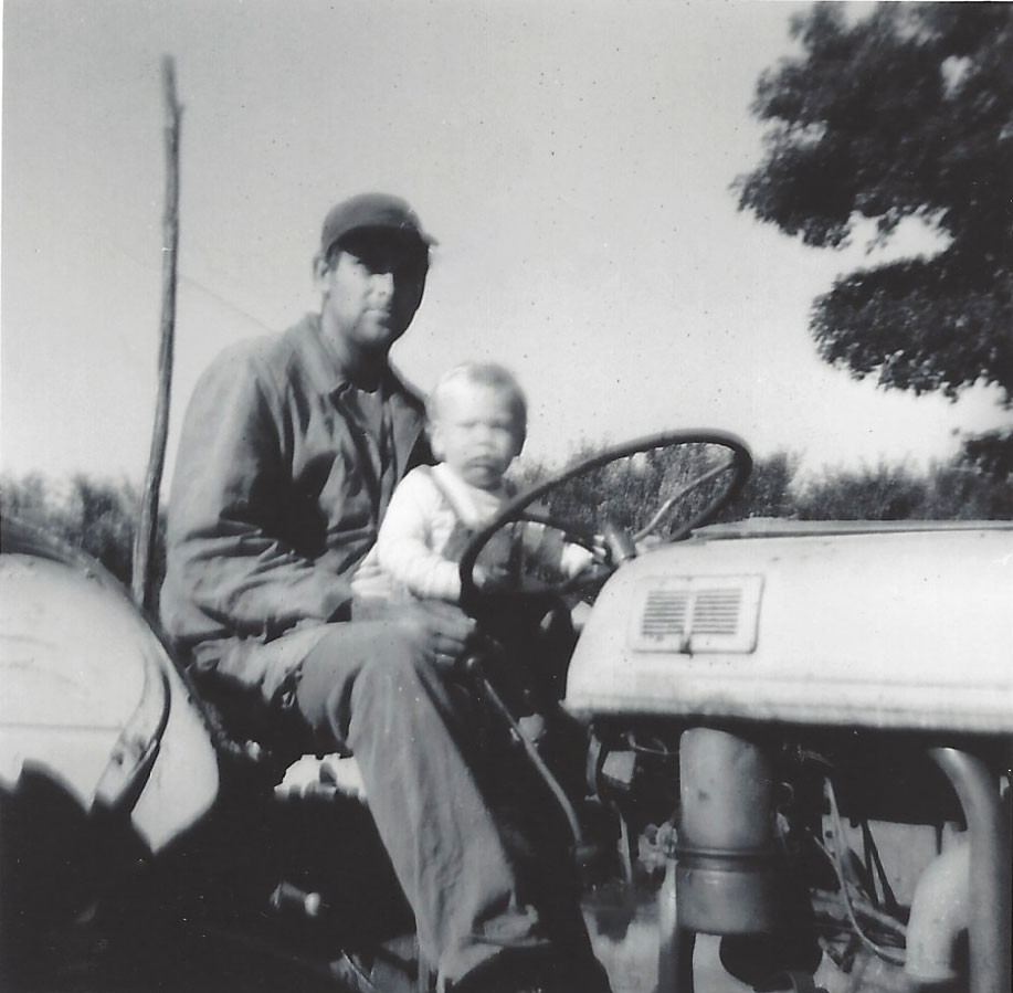 Black and white photo of Paul mason driving a tractor with a baby in his lap