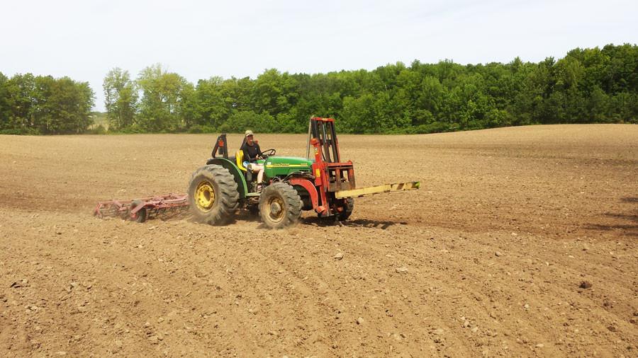 Tori Mason on a tractor tilling a field
