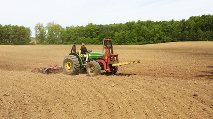 Tori Mason on a tractor tilling a field