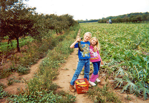 Lewis and Tori standing in a squash field holding squash