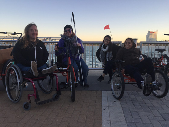 Four DDP members in front of the Detroit River testing out MoGo's adaptive bike options. Dessa sits in her wheelchair.