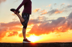 Running runner woman stretching leg muscle preparing for sunset trail run in outdoor summer nature.