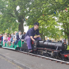 Black 5 with passengers with track along the pavement