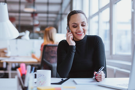 Happy young woman sitting at her desk wo