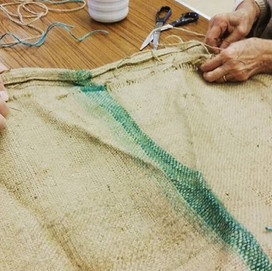 Collaborating with Muto and vulnerable members of the community to sew coffee sacks for food growing