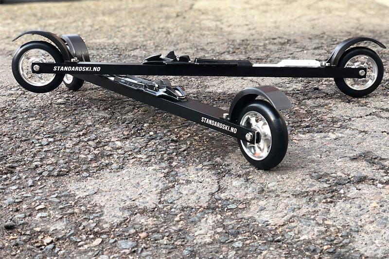 bilde av to sorte rulleski fra standard ski med laser markert logo skia ligger på asfalten