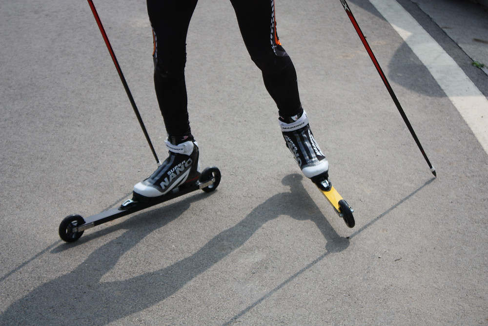 Bilde av bene til en som går på rulleski skate der den ene skia er sort den andre skia er gul, bakgrunnen er fra asfalten, utøveren har på seg sort tights.