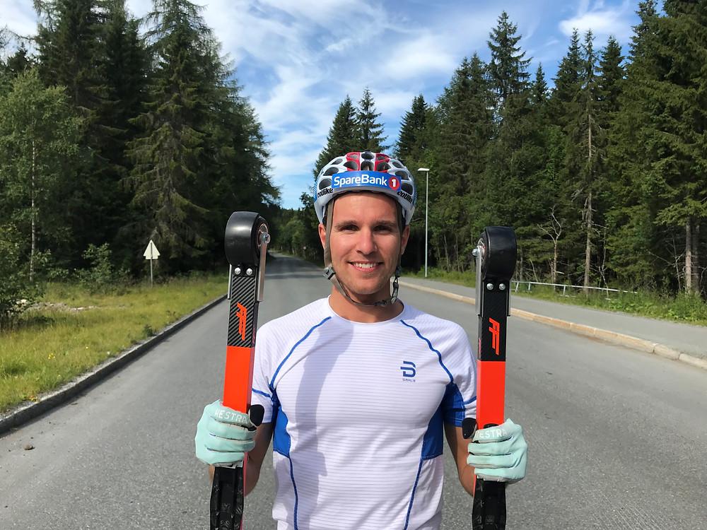 Didrik Tønseth holder opp for å vise frem FF Classic rulleskia, han holder en ski i hver hånd. Står på en rulleski bane med hjelmen på. i bakgrunn ser man skog og asfalt