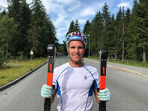Didrik Tønseth holding up FF Classic in each hand bakground is in the rollerski track
