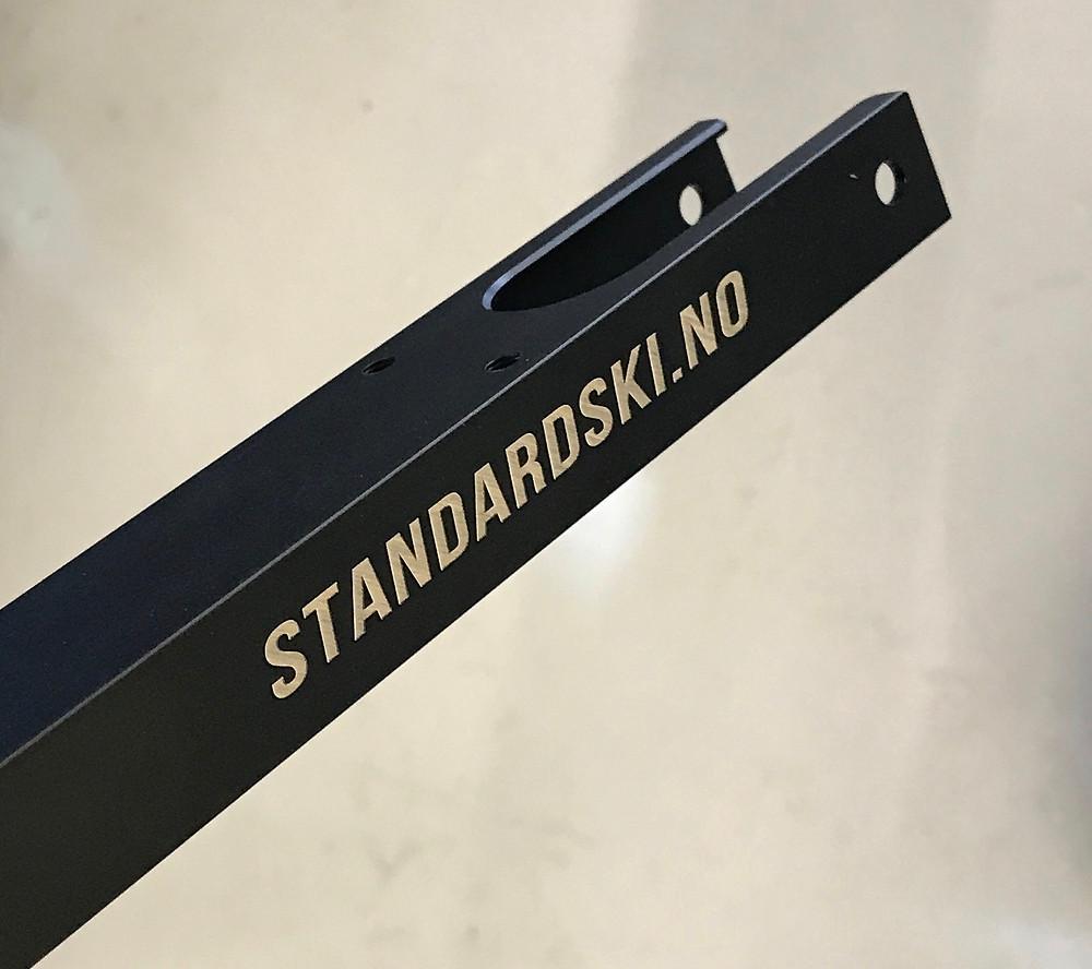 Nærbilde av en standard ski rulleski ramme i sort med hvit inngravert logo standardski.no