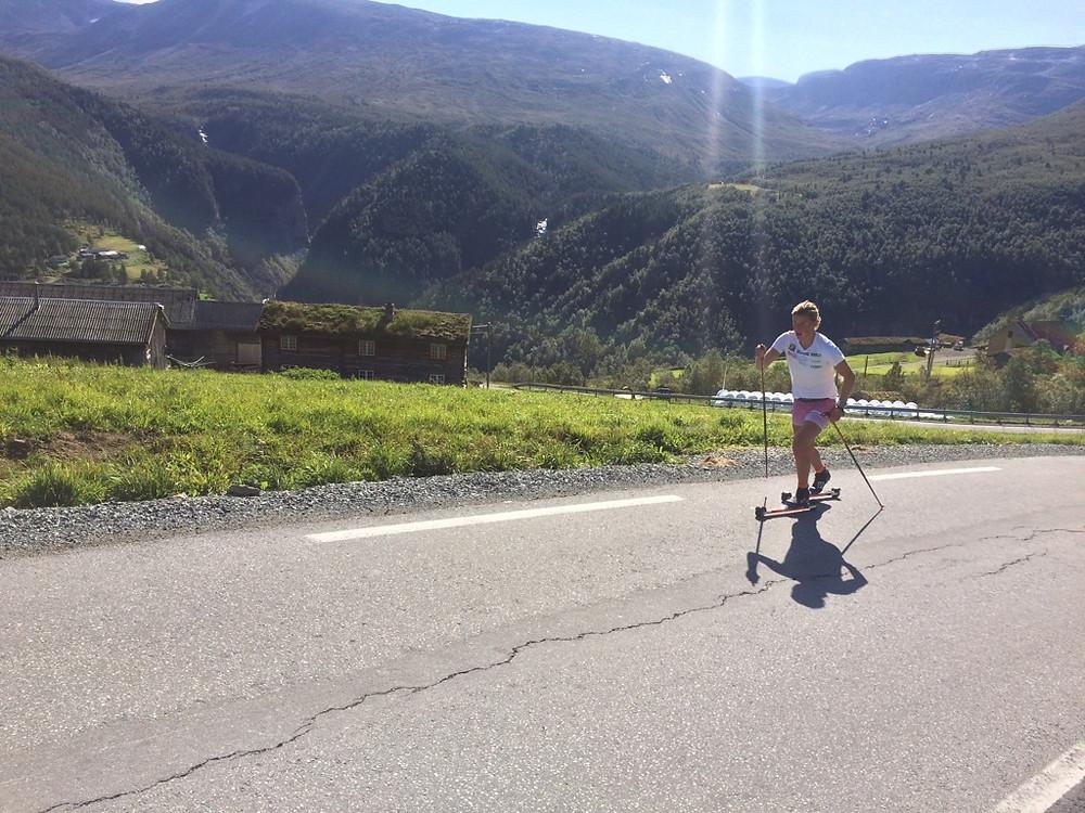 utsiktbilde med Karia Øyre Slind som tester FF Classic rulleski, hun kommer i full sprang oppover bakken.