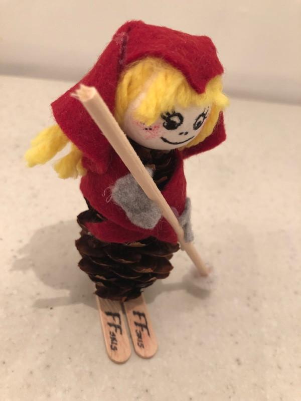 bilde av en selvlaget jente nisse med gult hår og rød lue, bene er en kongle og skia er to ispinner med logoen ff skis på
