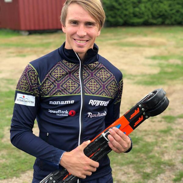 Karstein Johaug holder to par med ff skate på sag har han Team Telemark genseren.
