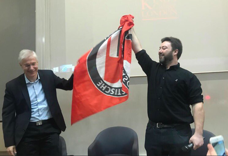 Sargon holding captured flag in victory.