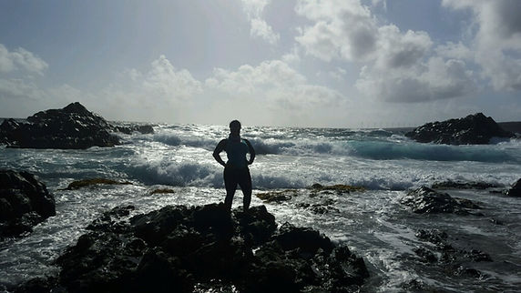 Leslie standing on a rocky outcrop on a beach in Aruba with waves crashing in the background