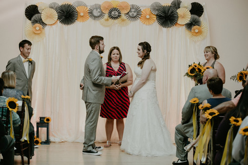 Jeff & Allie exchange vows under an arch of custom made pinwheels.  Photo Courtesy of Jacoby Photo & Design