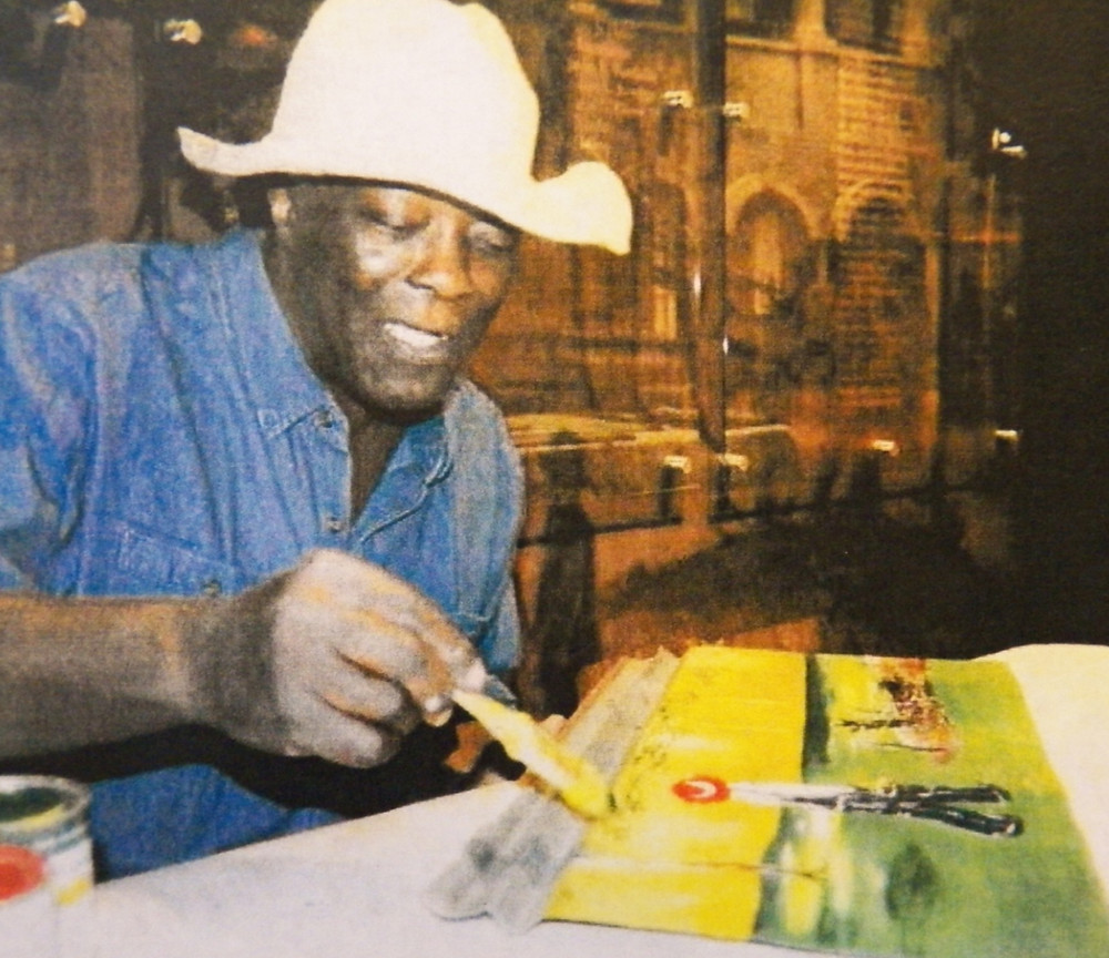 In a rare appearance, Leonard Jones demonstrates his painting technique using broken sticks as brushes.