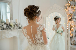 Beautiful bride in a wedding dress at a mirror in Christmas. Girl repeats the hairstyle and makeup.