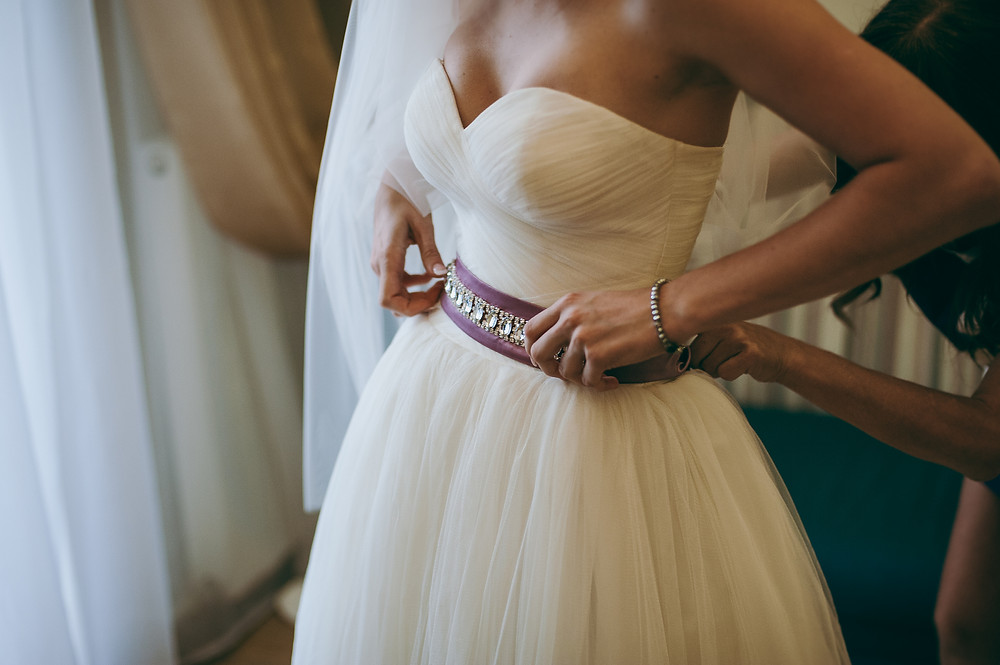Bride trying on a beaded belt on a wedding ballgown