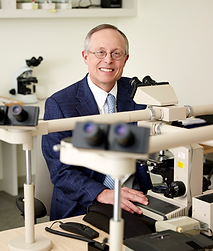 Picture of Clay J. Cockerell, MD sitting at the microscope.