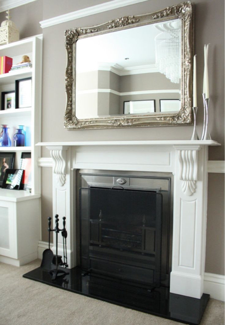 a mirror over a fireplace, decluttered mantel