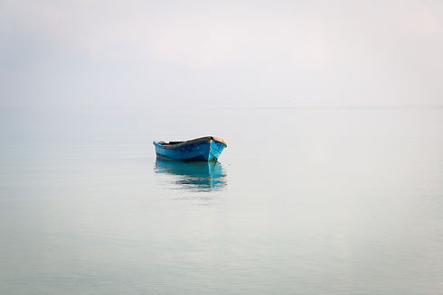single blue boat in water.jpeg