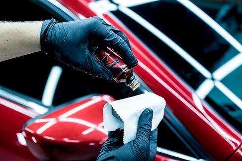 Car service worker applying nano coating on a car detail..jpg