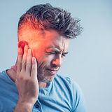 male having ear pain touching his painfu