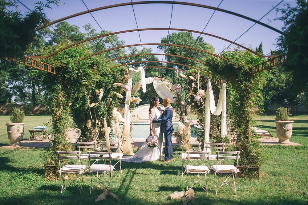 Des mariés sous une arche fleuri pour se dire oui lors d'une cérémonie laïque de mariage