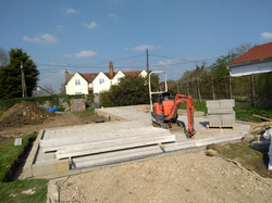 The floor beams are lifted into place with a small digger