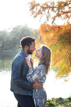 Un jeune couple se tient debout devant un lac. Ils se sourient. Ses mains à elle sont sur son torse et lui la tient par la taille. L'image est douce et lumineuse. les branches et les feuilles d'un arbre sont visibles et ont les couleurs de l'automne. jaune et orange.