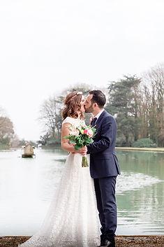 Un couple de mariés s'embrasse, debout, devant un étang. La mariée porte une robe blanche et tient son bouquet. le marié porte un costume foncé et tient la mariée par la taille. L'image est lumineuse.