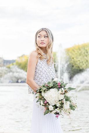 une mariée tient un bouquet de fleurs près dans le jardin du Palais Royal à Paris